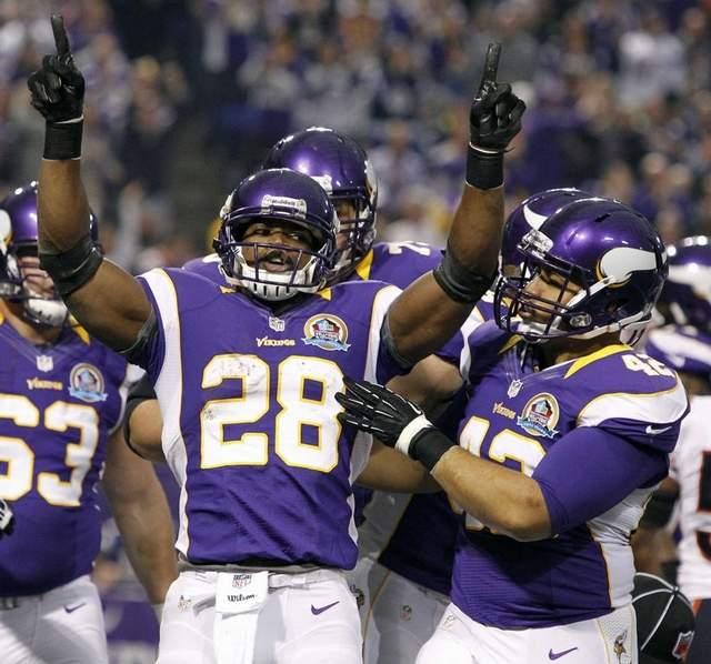 Vikings running back Adrian Peterson celebrates after one of his 13 touchdowns. (Genevieve Ross/Associated Press)