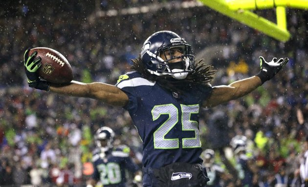 Richard Sherman celebrates afer a pick-six against the 49ers in front of the Seahawks' 12th Man -- their fans. (Associated Press/Elaine Thompson)