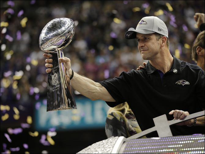 Jim Harbaugh celebrates with the Lombardi Trophy moments after winning the biggest game of his coaching career. (Associated Press)