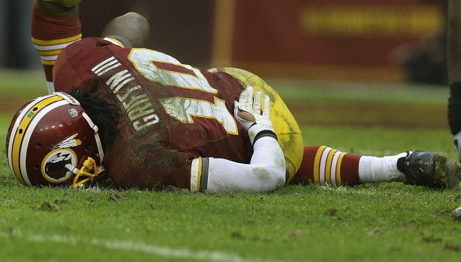 Robert Griffin III lays on the Redskins' deteriorated NFL turf after tearing his ACL. (AP Photo/Alex Brandon)